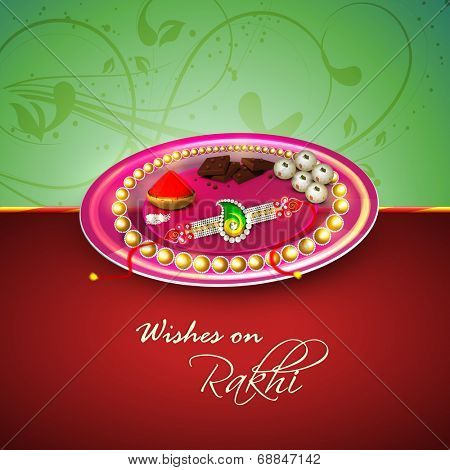 Beautiful Raksha Bandhan thali (plate) on floral decorated green and maroon background for the occasion of Raksha Bandhan celebrations.