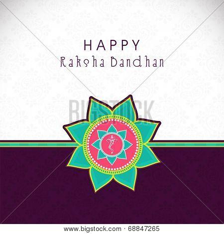 Beautiful rakhi on brown and grey background for Raksha Bandhan celebrations.