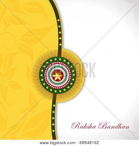 Beautiful rakhi on floral decorated yellow and grey background for Happy Raksha Bandhan celebrations.