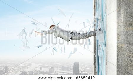 Businessman jumping through glass window of office