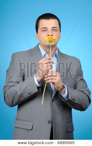 Handsome businessman holding gerber flower