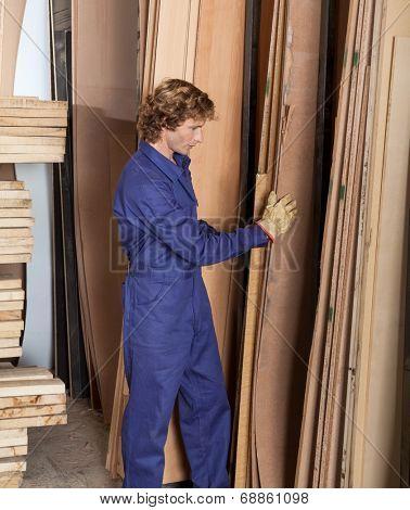 Full length side view of carpenter arranging wooden planks in workshop