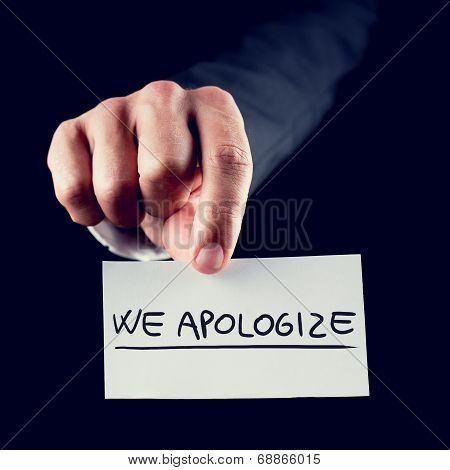 Businessman Holding A Card Reading We Apologise