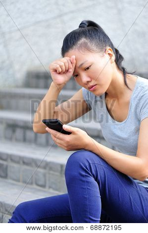 lonely young asian woman hold smart phone sit on stairs