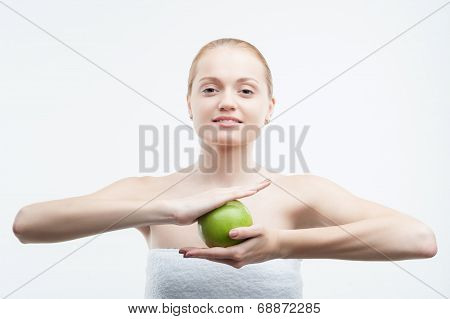 Portrait of young attractive woman holding a green apple