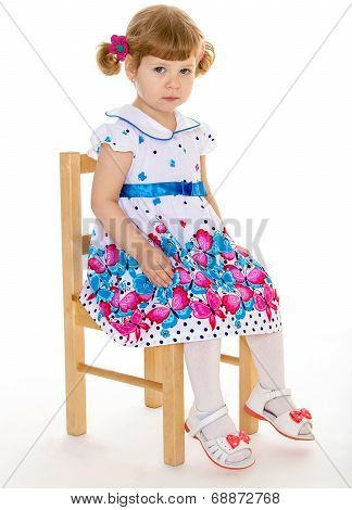 Beautiful little girl with beautiful pigtails pigtails sitting on a chair.