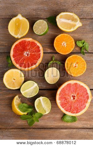 Different sliced juicy citrus fruits on wooden table