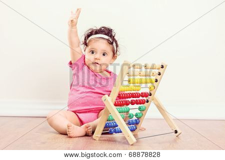 Baby girl sitting on floor and raising her hand with an abacus beside her