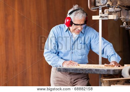 Senior carpenter cutting wood with bandsaw in workshop