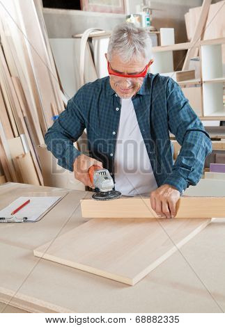 Senior carpenter using electric sander on wood at table in workshop