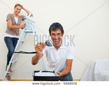 Smiling Couple Painting A Wall