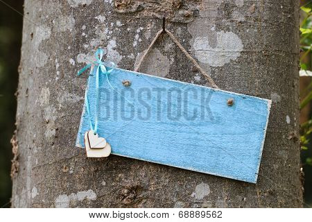 Blank blue sign with hearts hanging on tree in forest