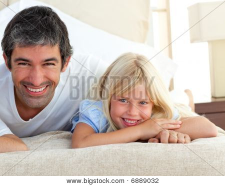 Smiling Little Girl Having Fun With Her Father Lying On Bed