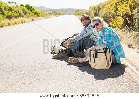 Attractive couple sitting on the road waiting for a lift on a sunny day