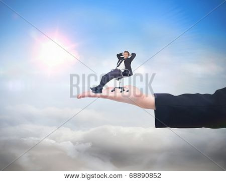 Businessman relaxing in swivel chair against blue sky with sunshine and clouds
