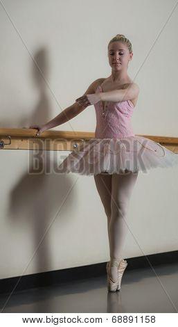 Beautiful ballerina standing en pointe holding barre in the dance studio
