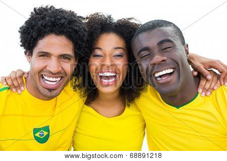 Happy brazilian football fans in yellow smiling at camera on white background