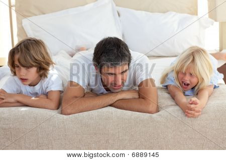 Father And His Children Talking Lying On Bed