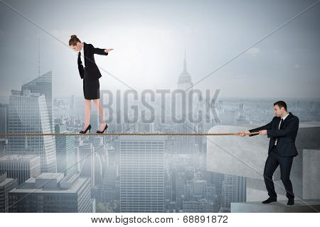Young businessman pulling a tightrope for business woman against misty cityscape