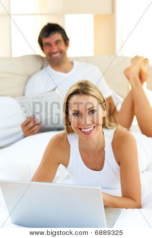 Smiling Couple Lying On Bed Using Computer