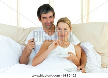Happy Couple Drinking Coffee Lying In The Bed