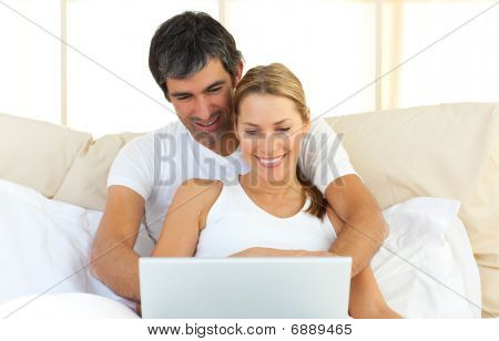 Enamoured Couple Using A Laptop Lying In The Bed