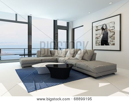 Waterfront living room with a bright airy lounge interior with a comfortable modern upholstered grey suite , art on the wall and a large panoramic view window along one wall overlooking the ocean
