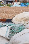 foto of nylons  - Large bags of nylon commercial fishing nets stored on a working beach in Hastings England - JPG