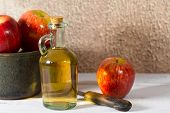 picture of vinegar  - Homemade Vinegar galas apples on a table in a farmhouse