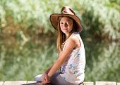 picture of baby cowboy  - Little girl with cowboy hat sitting on wooden dock beside river - JPG