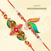 stock photo of rakhi  - Beautiful peacock feathers decorated rakhi on beige background for the occasion of Raksha Bandhan celebrations - JPG