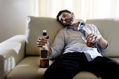 stock photo of sleeping  - drunk business man at home lying asleep on couch sleeping wasted holding whiskey bottle in alcoholism problem alcohol abuse and addiction concept looking grunge and sick in edgy radical studio lightning - JPG