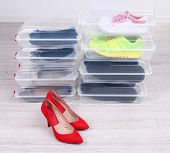 image of shoe-box  - Shoes in plastic boxes and female shoes on floor in room - JPG