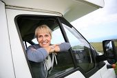 stock photo of motorhome  - Happy senior woman by motorhome window - JPG