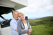 pic of motorhome  - Senior couple standing by motorhome in countryside - JPG