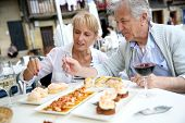 image of 70-year-old  - Senior couple eating Spanish fingerfood in Spain - JPG