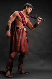 image of pirate sword  - a Scottish Lad stands holding a sword - JPG