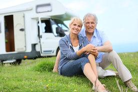 stock photo of camper  - Happy senior couple sitting in grass - JPG