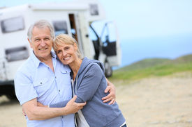stock photo of camper  - Cheerful senior couple standing by camper on road stop - JPG