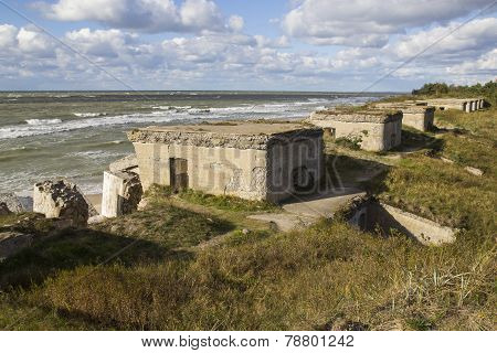 Remains of ruins of old fortification. Big concrete blocks on the seashore