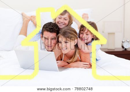 Loving family looking at a laptop lying down on bed against house outline
