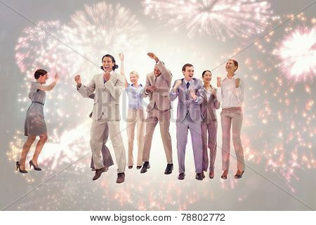 Very happy business people jumping and clenching their fists against colourful fireworks exploding on black background