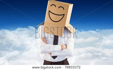 Anonymous businessman with arms crossed against bright blue sky over clouds