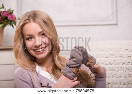 Young attractive woman holding baby mittens, interior shot