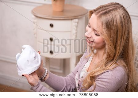 Young attractive woman holding baby hat, interior shot