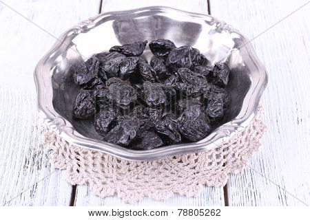 Metal plate of prunes on lace doily on color wooden background