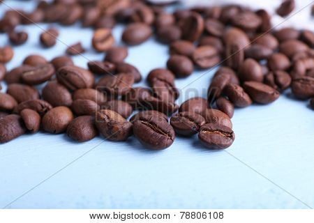 Coffee beans on the blue wooden background