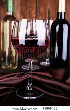 Red wine glass with bottles and glasses of wine close-up
