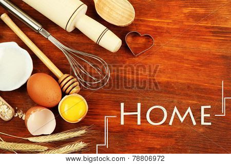 Home baking concept. Basic baking ingredients and kitchen tools on wooden table