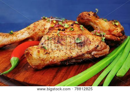 grilled meat : chicken quarters garnished with green onion pens and red peppers on wooden plate over blue wooden background